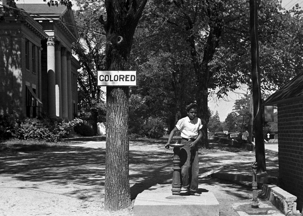 """Imagen de 1938, un niño bebiendo de una fuente para personas """"de color""""."""